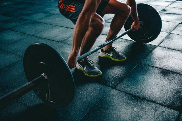 Mann mit Langhantel und Gewichten im Fitnesstudio